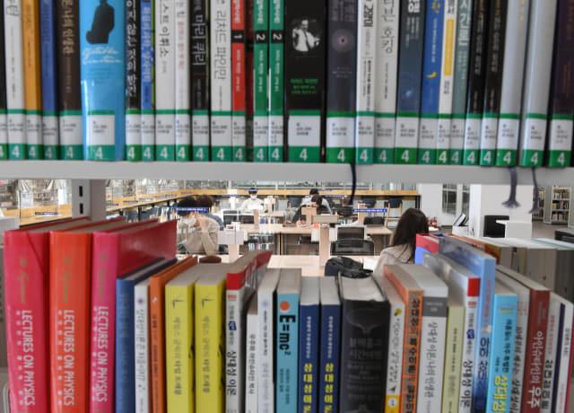 시민들이 칸막이가 설치된 일반자료실에서 책을 보고 있다.