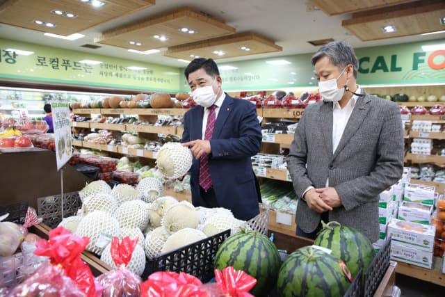 진주중부농협 심철효(왼쪽) 조합장과 김정곤 지점장이 로컬푸드 직매장 1호점에 진열된 과일을 살펴보고 있다.