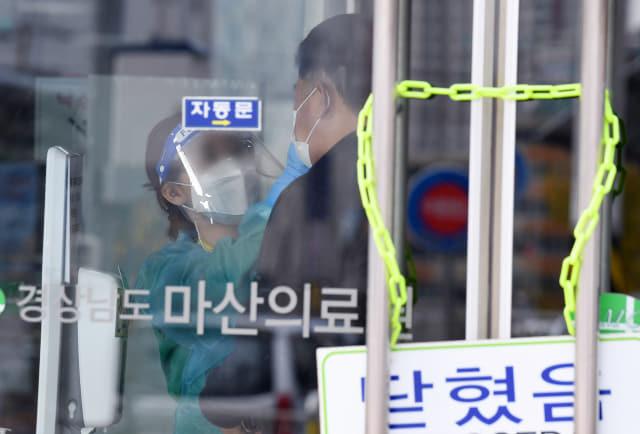 7일 오후 창원시 마산의료원 정문에서 한 의료진이 방문객의 체온을 측정하고 있다./김승권 기자/