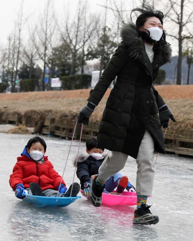 11일 오후 창원시 성산구 반림동 창원천에서 아이젠을 착용한 엄마가 아이들을 태운 썰매를 끌고 있다./김승권 기자/