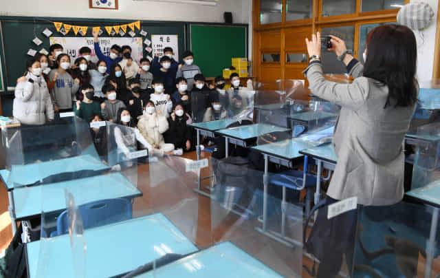 19일 창원시 의창구 용남초등학교 6학년 교실에서 졸업식을 마친 학생들과 교사가 칸막이 책상을 치운 후 기념촬영을 하고 있다. 이날 졸업식은 코로나19 감염 예방을 위해 학부모들은 참석하지 못했다./김승권 기자/