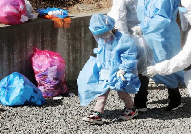신종 코로나바이러스 감염증(코로나19) 집단 확진이 발생한 광주 광산구 운남동 광주 TCS 국제학교에서 한 어린이가 몸에 맞지 않은 방호복을 입고 치료센터 이송 버스로 향하고 있다. 이곳에서는 120여명이 합숙 생활을 하다가 113명이 코로나19에 확진됐다. 연합뉴스