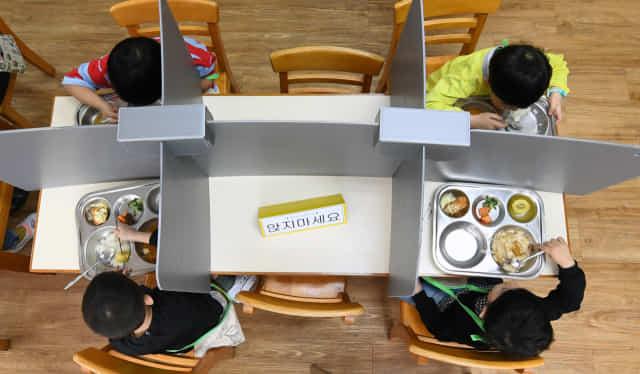 지난해 5월 창원 외동초에서 칸막이가 설치된 급식소에서 점심을 먹고 있는 학생들.
