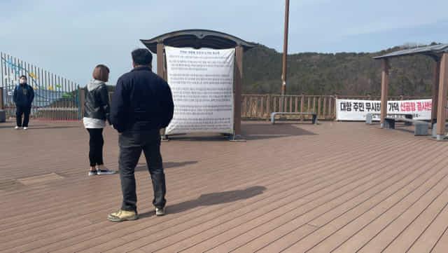 23일 가덕도 대항전망대를 방문한 사람들이 가덕도 주민들이 쓴 가덕 신공항 건설 반대 호소문을 읽고 있다.