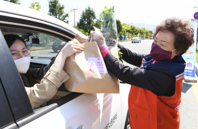 코로나19 장기화로 시민들은 드라이브스루 마켓에서 상품을 구입하는 일에 익숙해졌다. 사진은 지난해 4월 한 자원봉사자가 코로나19 피해농가돕기 친환경 쌈꾸러미를 판매하고 있는 모습.