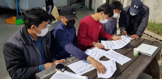 23일 낮 1시께 김해시 진영읍 한 공장에서 미얀마 이주노동자들이 현지에 보낼 응원 메세지를 작성하고 있다.