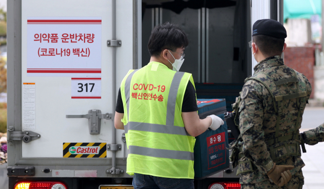 코로나19 백신 접종을 하루 앞둔 25일 오전 창원시보건소에서 군인의 삼엄한 경비 속에 방역 당국 관계자가 아스트라제네카 백신을 운반차량에서 꺼내고 있다./성승건 기자/