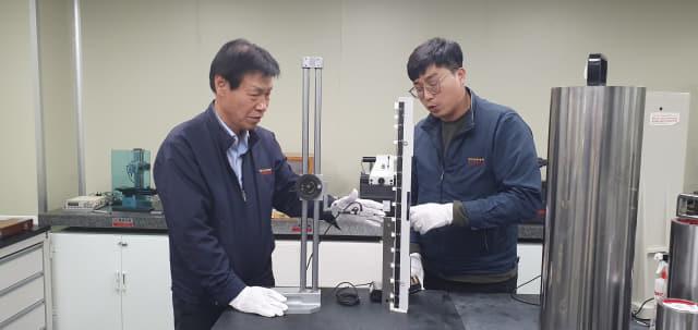 이문구(왼쪽) 대표가 전기마이크로미터와 게이지블록을 이용해 캘리퍼경사기 비교 교정을 하고 있다.
