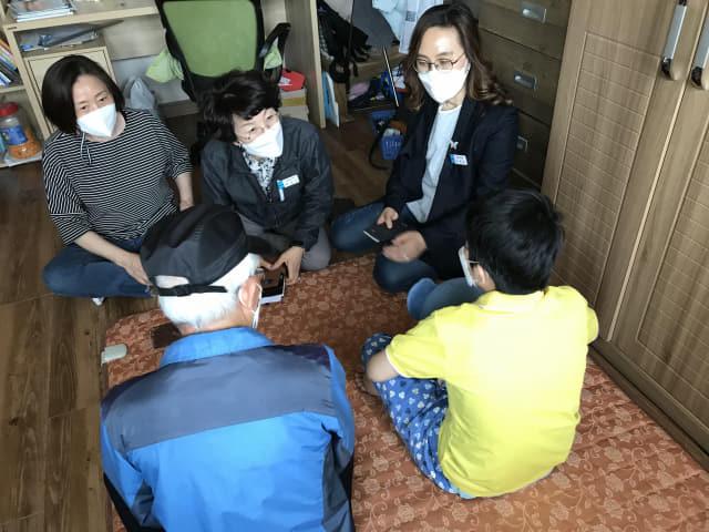 지난달 28일 창원시 마산회원구에 사는 부자와 구청 사회복지 담당자들이 이야기를 나누고 있다.