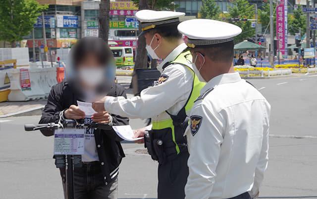 13일 오후 경남대학교 앞에서 경찰이 안전모를 착용하지 않고 전동킥보드를 이용한 시민을 적발해 계도하고 있다.
