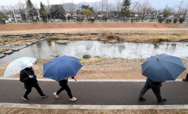 창원시 성산구 창원천 산책로에 우산을 든 시민들이 산책을 즐기고 있다./경남신문 자료사진/