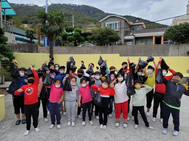 욕지도 특산물인 고구마 수확 체험을 마친 원량초등학교 전교생들이 직접 호미로 캔 고구마를 들어보이고 있다./원량초/