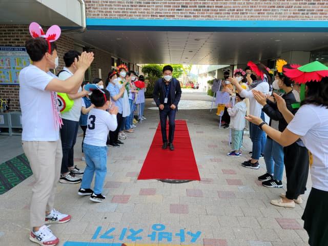 지난 14일 통영 충무공초에서 학부모와 학생들이 출근하는 선생님을 맞고 있다./충무공초/
