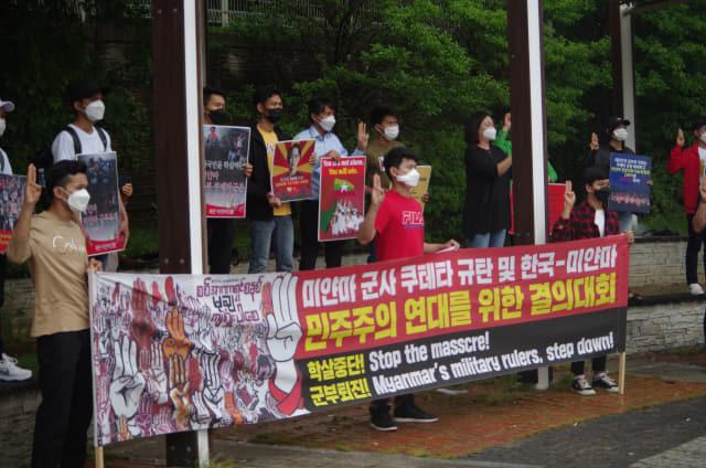 16일 오후 창원역 앞에서 열린 미얀마 민주주의 연대 11차 일요시위에서 미얀마 교민들이 미얀마 군부 독재에 대한 저항을 상징하는 세 손가락 경례를 하고 있다.
