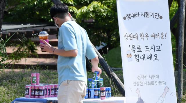9일 오후 창원대에서 한 동아리가 시험기간 학생들을 응원하기 위해 설치한 무료 음료대를 학생이 이용하고 있다./김승권 기자/