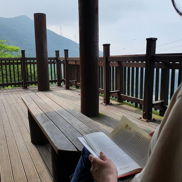 안민고개 전망대에서 한 시민이 한뼘도서관에서 꺼낸 책을 읽고 있다.