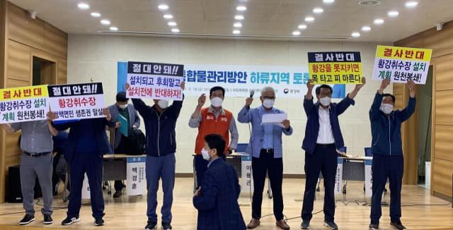 지난 18일 창녕군 국립생태원 습지센터에서 정부의 '낙동강 통합물관리방안'에 반대하는 주민들이 하류지역 공개토론회 단상을 점거한채 시위를 벌이고 있다./경남신문 DB/
