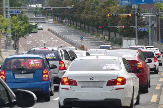 21일 오후 3시 월영마린애시앙 후문 앞 도로에서 '송전탑 지중선로 반대' 등의 피켓을 부착한 차량 50여대가 차량 시위를 벌이고 있다.