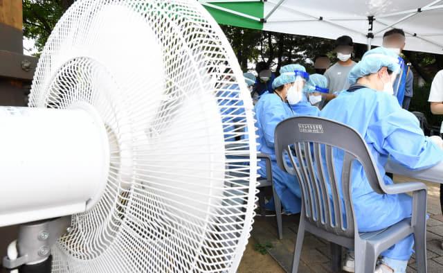 25일 오후 창원시 의창구 팔용미관광장에 마련된 외국인 임시선별진료소에서 의료진이 폭염 속 선풍기에 의지한 채 현장 접수를 받고 있다./성승건 기자/