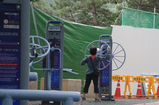 3일 오전 11시께 창원 월영동 청량산 등산로 내 2번 송전탑 공사현장 앞에서 한 주민이 야외운동기구로 운동을 하고 있다./김용락 기자/