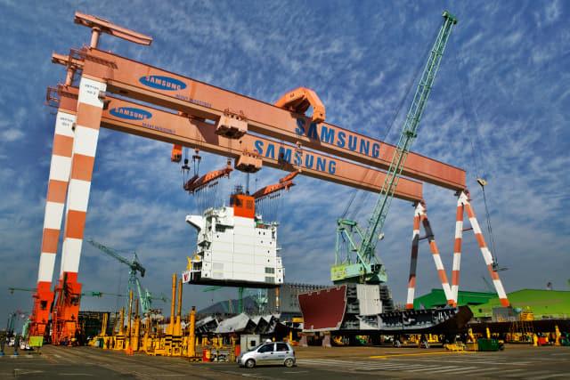 삼성중공업 거제조선소에 설치된 골리앗 크레인이 대형 선박 구조물을 들어올려 조립지점으로 옮기고 있다.