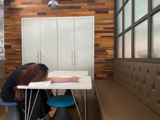 한 대학생이 취업 공부를 하다 지쳐 엎드려 있다.