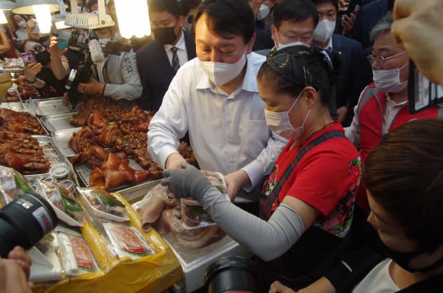 윤석열 국민의힘 대선 경선 후보가 18일 오후 3시께 창원시 마산합포구 마산어시장에서 한 상인으로부터 족발을 구매하고 있다./김용락 기자/