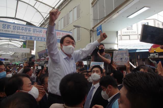 18일 오후 3시께 창원시 마산합포구 마산어시장을 찾은 윤석열 국민의힘 대선 경선 후보가 간이의자 위에 올라가 정권교체를 외치며 시민들의 지지를 호소하고 있다./김용락 기자/