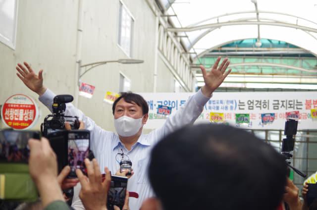 18일 오후 3시께 창원시 마산합포구 마산어시장을 찾은 윤석열 국민의힘 대선 경선 후보가 간이의자 위에 올라가 두 팔을 펼치며 시민들의 지지를 호소하고 있다./김용락 기자/