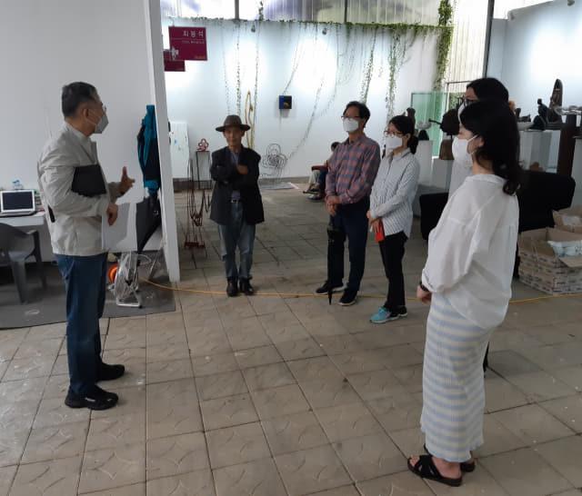 남가람박물관 이성석 관장이 마산현대미술관 입주작가들의 오픈 스튜디오를 방문해 예술가가 가져야 할 사명감에 대해 설명하고 있다./주재옥 기자/