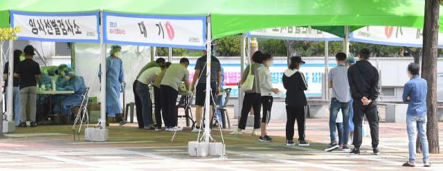 26일 창원종합버스터미널 앞 임시선별검사소에서 시민들이 코로나19 검사를 받기 위해 기다리고 있다./김승권 기자/