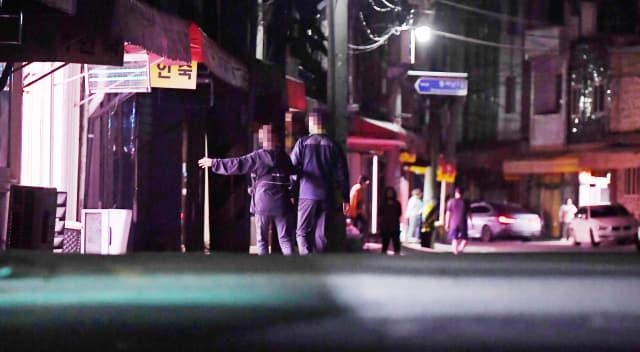 지난 25일 밤 창원시 마산합포구 서성동 성매매 집결지에서 한 업주가 남성에게 다가가 호객 행위를 하고 있다./김승권 기자/